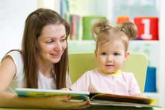 Kid girl and mother read a book indoors Stock Images