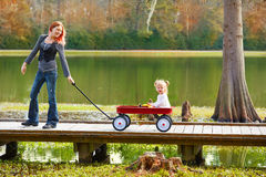 Kid girl and mother walking in lake with pull cart Royalty Free Stock Photos