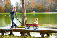 Kid girl and mother walking in lake with pull cart Stock Image