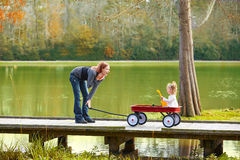 Kid girl and mother walking in lake with pull cart Royalty Free Stock Image