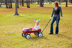 Kid girl and mother walking in park with pull cart Royalty Free Stock Images