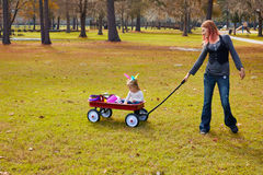 Kid girl and mother walking in park with pull cart Stock Photo