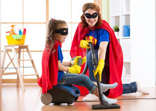 Kid girl and mother weared Superhero costumes. Cute helper child and woman make cleaning room and have a fun. Royalty Free Stock Image