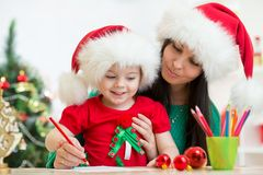 Kid girl and mother writing letter to Santa Royalty Free Stock Image