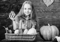Kid girl near basket full of fresh vegetables harvest rustic style. Farm market fall harvest. Child girl presenting. Harvest of her vegetable garden on wooden royalty free stock image