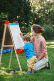 Kid girl with older sister, teacher standing outside in summer autumn park drawing on easel with markers, playing studying Royalty Free Stock Photography