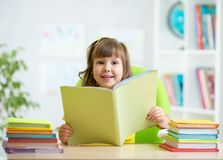 Kid girl with opened book at home Stock Image