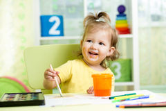 Kid girl painting on paper in nursery Stock Images