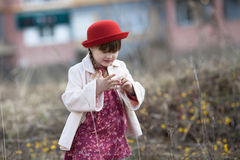Kid girl with pigtails in hat walks on spring park Royalty Free Stock Photo