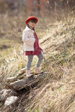 Kid girl with pigtails in hat walks on spring park Royalty Free Stock Photography