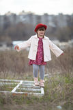 Kid girl with pigtails in hat walks on spring park Stock Image