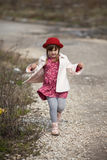 Kid girl with pigtails in hat walks on spring park Stock Photo