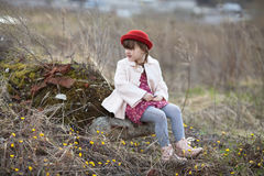 Kid girl with pigtails in hat walks on spring park. Funny child girl with pigtails in hat and coat walks on spring park childhood lifestyle Royalty Free Stock Image