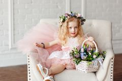 Kid - girl in a in a pink dress and flower crown. Beautiful little girl in a bright studio sits, lauht and looks into stock photography
