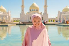 Kid girl in pink hijab sits next to a white mosque and smiles. On the street royalty free stock photo