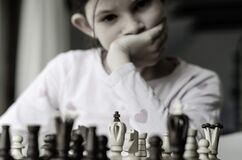 Free Kid Girl Playing Chess, Looking At Chess Board And Thinking About Her Next Move Stock Image - 183327781
