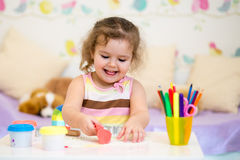 Kid girl playing with colorful clay Stock Images