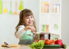Kid girl playing cook and makes a dinner stock photo