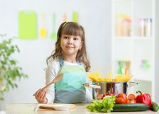 Kid girl playing cook and preparing spaghetti Royalty Free Stock Image