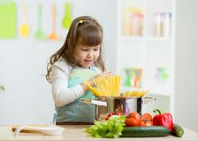Kid girl playing cook and preparing spaghetti Stock Photography