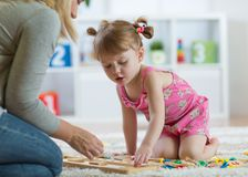 Kid girl playing with developmental toys at home or kindergarten stock image