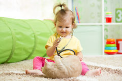 Kid girl playing doctor with kitten Royalty Free Stock Images