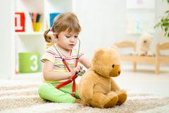 Kid girl playing doctor with plush toy at home Stock Photos