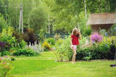 Kid girl playing with garden sprinkler in hot summer day Stock Images