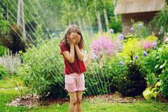Kid girl playing with garden sprinkler in hot summer day Royalty Free Stock Photos