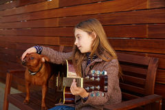 Kid girl playing guitar with dog and winter beret Royalty Free Stock Photography