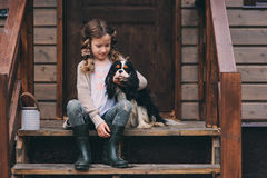 Kid girl playing with her spaniel dog, sitting on stairs at wooden log cabin Royalty Free Stock Image