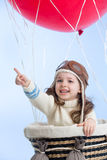 Kid girl playing on hot air balloon on the sky. Background stock image