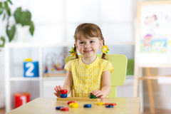 Kid girl playing with logical toy on desk in nursery room or kindergarten. Child arranging and sorting colors and sizes Royalty Free Stock Images