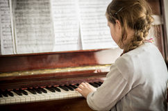 Kid girl playing on piano royalty free stock photo