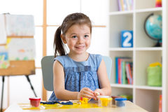 Kid girl playing with plasticine at home Stock Image
