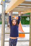 Kid girl playing in playground  hanging from wood bars. Smiling happy Stock Image