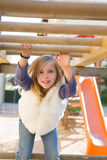 Kid girl playing in playground  hanging from wood bars. Smiling happy Royalty Free Stock Photography