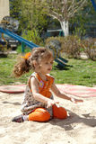 Kid girl playing in a sandpit Stock Photos
