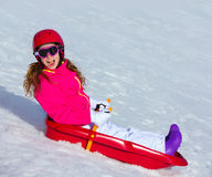 Kid girl playing sled in winter snow Royalty Free Stock Photo