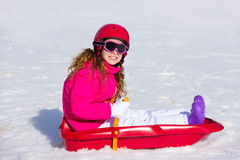 Kid girl playing sled in winter snow Royalty Free Stock Image