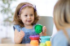 Kid with teacher in kindergarten stock photo
