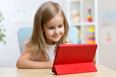 Kid girl playing with tablet computer at home Royalty Free Stock Photo