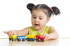Kid girl playing with train toy. Isolated on white Stock Image