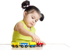 Kid girl playing with train toy. Isolated on white Royalty Free Stock Image