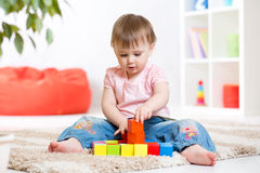 Kid girl playing wooden block toys Royalty Free Stock Images