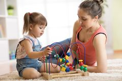 Kid girl plays with educational toy indoor. Happy mother teaching her smart daughter. Child girl plays with educational toy indoor. Happy mother teaching her stock images