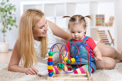 Kid girl plays with educational toy indoor. Happy Stock Photography