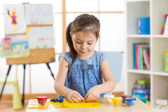 Kid girl plays plasticine or dough at home in her room Royalty Free Stock Image
