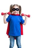 Kid girl plays superhero and lifts dumbbells Stock Image