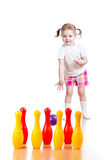 Kid girl plays and throws ball to pins Stock Image